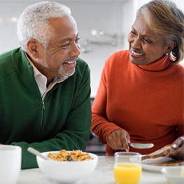 Picture of a happy senior couple, talking and laughing while enjoying breakfast