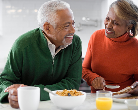 Picture of a senior couple, talking and laughing while eating breakfast