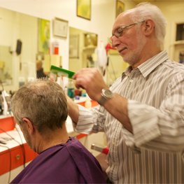 Picture of a barber, comb and scissors in hand, cutting another gentlman's hair
