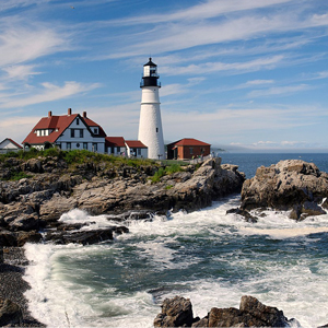 A lighthouse on a seaside rocky shore in Maine.