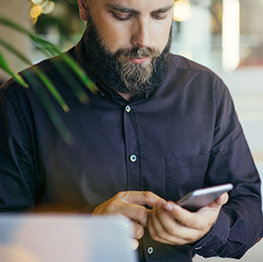 Picture of a young bearded man holding a smartphone