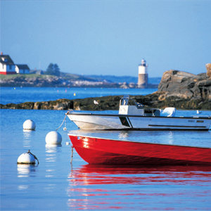 Picture of small boats and buoys in Boothbay harbor with lighthouse in the background