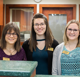 Picture of team of tellers at the bank's Woodsville Walmart office, three young ladies standing side by side and smiling at the camera